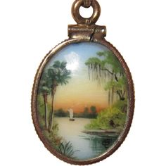 This miniature painting is the work of Olive Wesler Commons, who, along with her husband, moved from Indiana to an island on the St. Johns River in central Florida in 1908. Every window in her island home framed a magnificent view. She began sketching the rugged grace of live oak trees in a smoky drift of Spanish moss; the splendor of sunset and dawn across the water; the beauty of palms and pines and sea birds in flight. One day she painted one of these scenes on a small porcelain…
