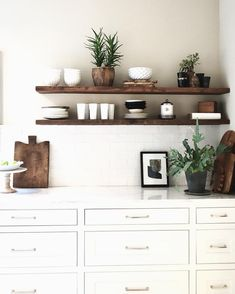 Contemporary floating shelves above white tile & cabinets | White & wood | by Carol Estes