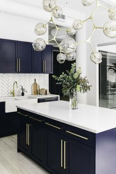 Brighter color scheme - More bold navy shaker style cabinetry, white marble counter tops, white heringbone splash back and a statement kitchen island pendant.