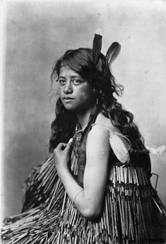 Maori woman wearing a piupiu, with feathers in her hair and a bracelet on her arm. She holds a poi.
