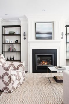 Beautiful living room boasts an armchair, complete with a white and gray medallion print slipcover, facing a marble top rectangular coffee table atop a West Elm Jute Herringbone Chenille Rug. Fireplace Surrounds, Fireplace Design, Fireplace Mantle, Black Fireplace, Fireplace Bookcase, Simple Fireplace, Fireplace Stone, Modern Fireplace, Fireplace Ideas