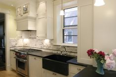 White cabinets, black apron front sink