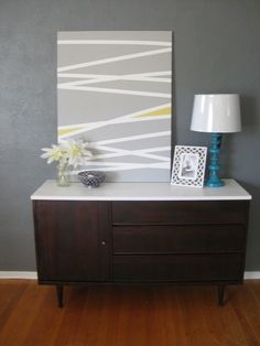 Another take on the DIY masking tape stripe art - paint a couple sections in an accent colour. Really like this idea to create your own piece of artwork using the colours or contrasting colours of a room.