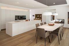 Cucina moderna bianca, con isola e tavolo da pranzo, con pavimenti in legno colore chiaro - Idea ristrutturazione cucina