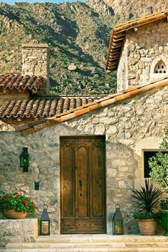 love everything about this: stone walls, architecture, wooden door and lanterns…