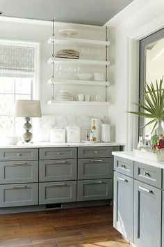 updating white kitchens - white kitchen with gray base cabinets - southern living via atticmag