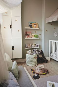 Put together a cozy activity space in the nursery with a rack for books a cozy sack of soft toys and some textile mattresses.