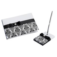 <div>The dramatic damask pattern on this guest book and pen holder is perfect for the modern bri...