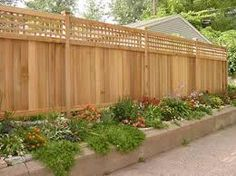 this fence provides privacy with the extra height gained from the flower bed which in turn