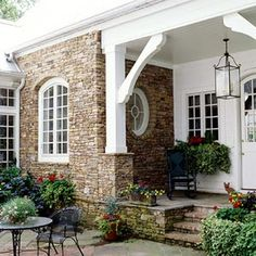 love this porch with the stonework and oval window, the beadboard ceiling and brackets