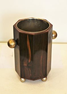 Art Deco cooler made of nickel-plated metal and covered with Macassar ebony veneer. There are two nickelled  handles on the sides, and four spheres serving as legs for the cooler.