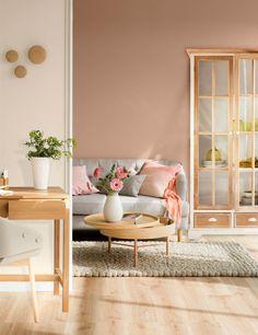 Salón con pared rosa y sofá gris con mesa de centro, consola y armario en madera clara