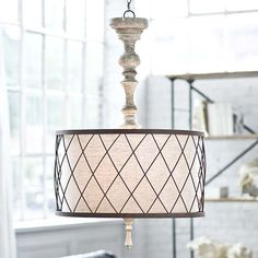 "Shaped like an upside down table lamp with a turned wooden base, the Gesso Spindle chandelier brings European charm to a dining room or foyer. Its neutral drum shade is accented with diamond-patterned ironwork for a rustic touch.Chandelier measures 24"" round x 37""H."