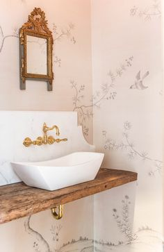 """The tiny powder room walls are covered in a peaceful scene with birds and butterfly's hand drawn in pencil on silk paper . The pattern is called """"Pencil"""" from Fromental. A 400 year old piece of wood compliments a new stone modern sink."""