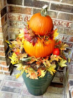 Fall container gardening idea with stacked pumpkins.