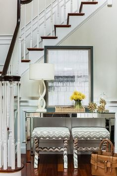 At the base of a white staircase accented with stained wood treads and a dark wood handrail, two white and gray x-stools sit beneath a mirrored console table positioned against white wainscoting accented with a pale gray upper wall. Interior Design Magazine, Interior Design Tips, Interior Inspiration, Design Inspiration, Monochrome Interior, Classic Interior, Staircase Interior Design, Erin Gates, Foyer Decorating
