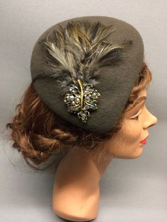 This desirable felt fascinator is the Lucille! It has an asymmetric shape and a sloping crown which forms a tear-drop shape. Trimmed with a beautiful vintage brooch and a feather pad complimenting the felt colour. Colour: Brown #Fabhatrix #Edinburgh #Grassmarket #felt #fascinator #occasion
