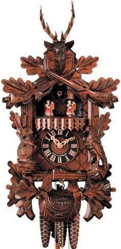 """Hones 17"""" 1 Day Carved Music 634/3T Cuckoo Clock – Meticulously etched, this clock is rightfully a piece of incredible artwork. It features the three signature animals of the Black Forest; deer, bird and rabbit. It also has leaves and branches woven into the architecture. It also features traditional dancers that one might have seen during the dawn of cuckoo clocks. You are guaranteed a Black Forest Seal with the purchase of this.  Designed in Time"""