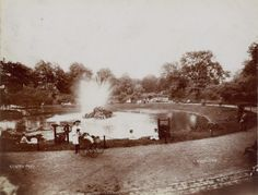 Benton Park, scene near lake with fountain. Young girl in foreground pushing wicker carriage with baby. (1900)