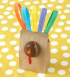 Thanksgiving craft: Start with the turkey's face by folding four punched brown card-stock circles in half and gluing the folds back-to-back to create the fanned head shape. Add an orange card-stock beak, a red card-stock wattle, and two googly eyes for facial features. Then ask your kids to write things they are thankful for on a variety of colored card-stock strips and attach them to the back of the folded-over bag top.