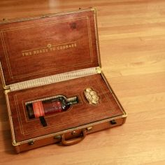 """""""The two roads to courage."""" A suitcase that holds nothing but a bottle of bourbon and a set of brass knuckles."""