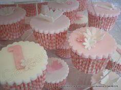 Christening and 1st birthday cupcakes with delicate sugar cutout details of flowers butterflies and number 1 pink and white shades in gingham cases