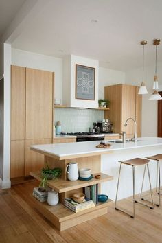 white modern kitchen with hanging lights and bar stools