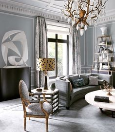 Timeless room with contemporary touches... fashionable grey colour, contemporary low table and couch, timeless shapes: obelisk-shaped open cabinet & obelisk-shaped table lamp - Jean-Louis Deniot Interiors.