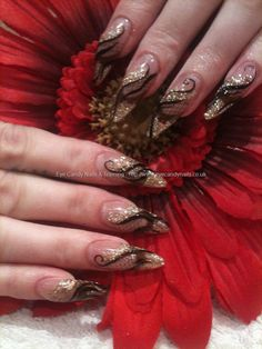 Stiletto nails with gold glitter and freehand nail art