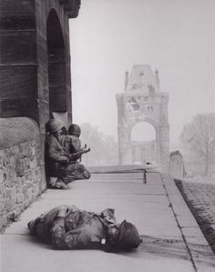 Two GIs take cover on the bridge at Worms Nibelungen, Germany on March 28, 1945, as snipers on the other bank of the Rhine take aim. In the foreground lies one of their victims.
