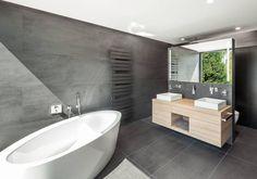 Gorgeous minimal bathroom with cool, modern freestanding bathtub and grey tile scheme. So cool. by ZHAC / Zweering Helmus Architekten
