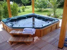 Awsome backyard jacuzzi hot tub on wooden deck with green garden view