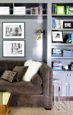 A comfortable, contemporary sofa sits in a nook surrounded by built-in bookcases. Touches of eclectic design are brought into the space with a gold trunk and Lucite side table. Pantone, Built In Bookcase, Bookcases, Bookshelf Styling, Interior Rugs, Gray Interior, Family Room Decorating, Decorating Ideas, Grey Room