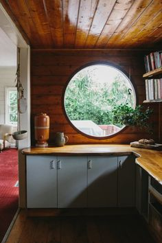 Gorgeous wood paneling and round window with mid century decor made this kitchen area the spotlight of the house. Old Cottage, Coastal Cottage, Coastal Decor, Coastal Living, Coastal Homes, Coastal Curtains, Coastal Entryway, Coastal Rugs, Coastal Bedding