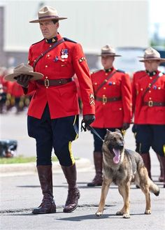 An officer holds Danny, the K9 partner of slain RCMP officer Const. David Ross, at the funeral procession for the three RCMP officers who were killed in the line of duty in Moncton, New Brunswick.