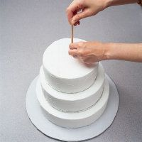 Push the sharp end of the dowel into center of top tier and carefully push down