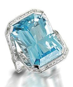 A topaz and diamond dress ring The rectangular-cut blue topaz, to a semi-surround and bifurcated shoulders inlaid with baguette-cut diamonds, mounted in 18k white gold, diamonds approximately 1.85 carats total