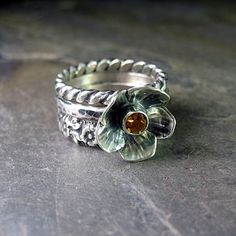 A sweet trio of sterling silver rings brings to mind a summer meadow full of daisies and black-eyed susans. Two patterned wire rings, one a circle of flowers, and the other a twist pattern, highlight a sweet silver buttercup with a center of faceted citrine. Perfect to mix and match