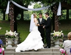 Trellis and urn arrangements showcased by bride and groom