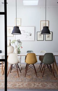 Scandinavian style in a modern dining room featuring a gallery wall of figure drawings and portrait artwork, black vintage industrial style pendant lights over a white table with a lightwood base, Eames side chairs in white, gray, and mustard yellow, and an antique woven area rug in grays, beige and gold - Eclectic Home Decor & Decorating Ideas - Scandinavian Interiors