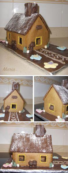 Casita de galleta de jengibre con figuritas de gato de chocolate y decoraciones de gominola. La casita está pegada con caramelo (azúcar fundido)
