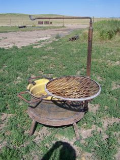 Fire pit made from a tractor wheel, grate and steel for holding pots