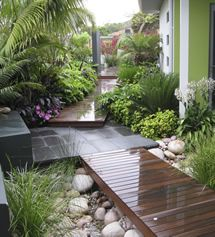 gorgeous mix of materials. layering and varying heights of the different plants and levels adds so much visual interest to a small narrow area