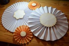 Paper rosettes in white and creme brulee (peach) available at AJ's Craft Creations. https://www.facebook.com/ajs.craft.creations