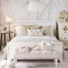Vintage glam bedroom, with tree-print wallpaper and white wooden bed