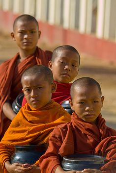 Four novice Monks in Myanmar. It's customary for a male in Myanmar to enter a monastery twice in his life. Once as a samanera, a novice monk, between the age of 10 and 20, and again as a hpongyi, a fully ordained monk, sometime at the age of 20. Some might remain a monk for just a few days, while others stay for life.