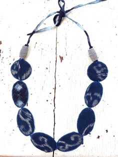 Ive used vintage Kasuri print textiles to create the wafer beads which I edge in embroidery thread. The necklace can hang down between 10 and 12 on either side depending on how you tie it. One of a kind necklace, made in the USA.