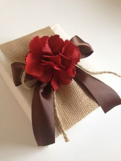 Bello presente lleno de lazos y flores rojo naranja fall present. brown ribbon, and a orange/red flower. lovely!