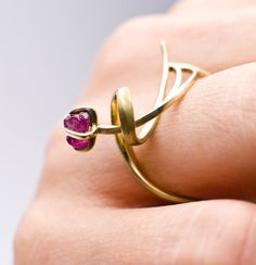 """Lucio Unccut, ring 1"" by Sarah Warsop. (on the body), 18ct gold, uncut ruby.Lucio Uncut began as a single commission to make an 18ct gold brooch with an uncut ruby. The piece was based on Lucio, the clients young son. From video Sarah studied his movement as he played, learning his particular rhythmic and dynamic qualities and choosing short phrases to learn....."