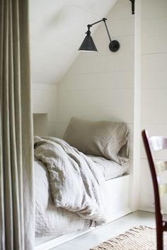 curtained off bed under sloped ceiling